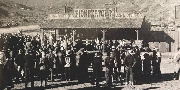 Crowd of people at the Land Office image. links to news articles about land development in Pioneertown.